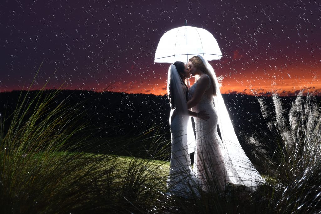 Brides Kissing Under Glowing Umbrella Sunset | Anna Christine Events Orlando Central Florida Wedding Planner