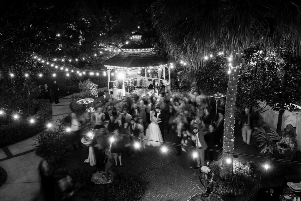 Bride & Groom Dancing Blurred Guests Reception | The Courtyard at Lake Lucerne Classic Purple & Orange Wedding Football Texas Longhorns Sports Lake Lucerne Courtyard Anna Christine Events Orlando Kathy Thomas Photography