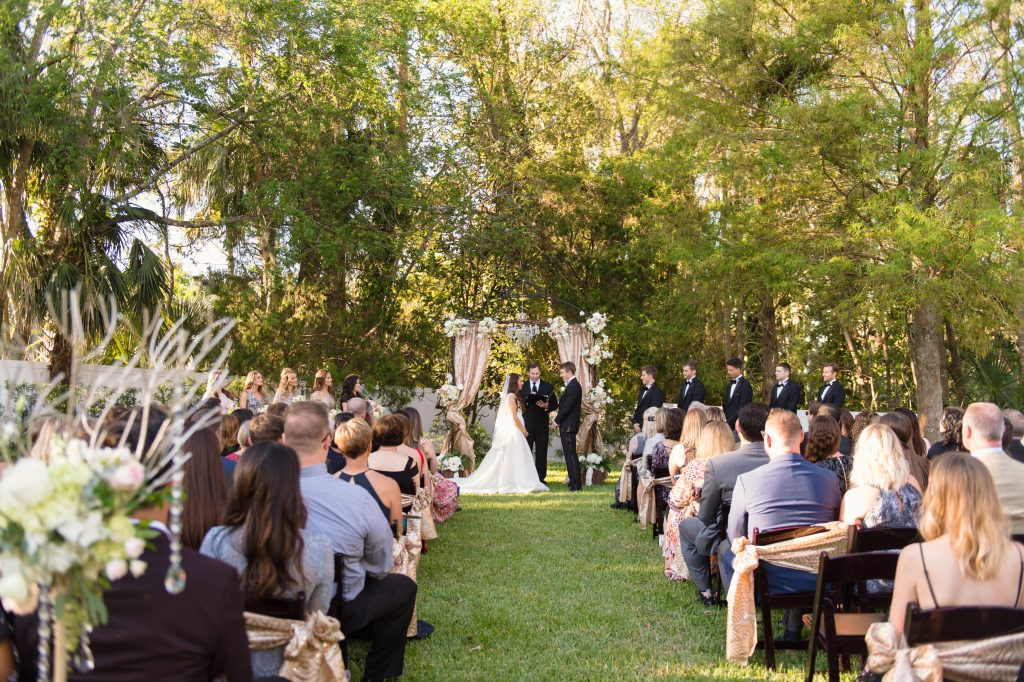 Bride & Groom at Arbor Outdoor Ceremony | Travel Inspired Themed Glamorous Gold & White Wedding Luxmore Grande Estate Anna Christine Events Justin DeMutiis Photography