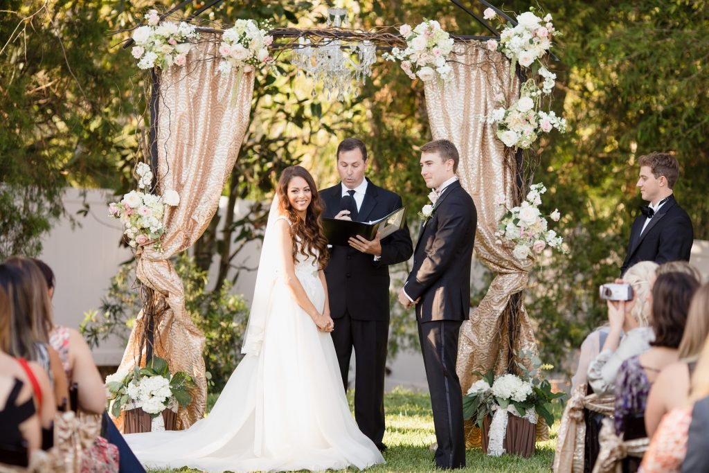 Bride & Groom at Archway Arbor Outdoor Ceremony | Travel Inspired Themed Glamorous Gold & White Wedding Luxmore Grande Estate Anna Christine Events Justin DeMutiis Photography
