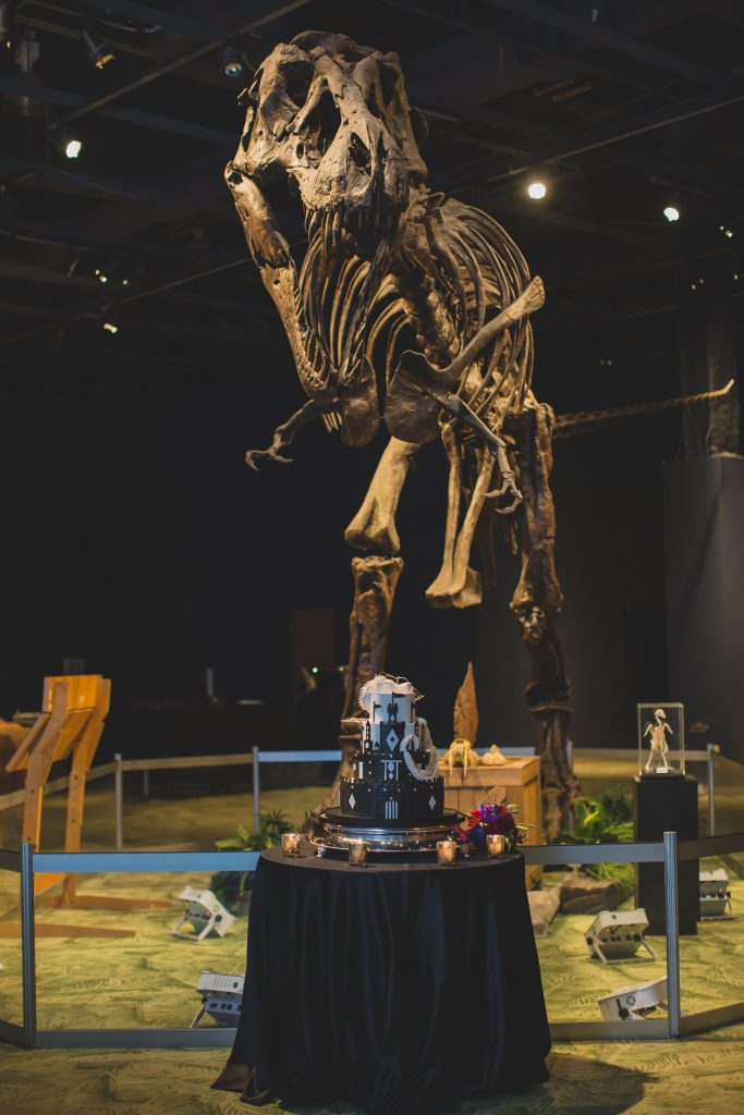 Dinosaur skeleton in front of Game of Thrones wedding cake | Nerd Geek Chic Wedding Theme Game of Thrones Harry Potter Super Mario Orlando Science Center Anna Christine Events Orlando Wedding Planner Ashley Jane Photography
