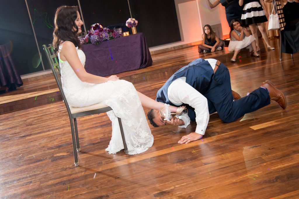 Groom getting garter Classic Purple & White Wedding Photography Noah's Event Venue Orlando Florida Anna Christine Events Wedding Planner Jessica Leigh