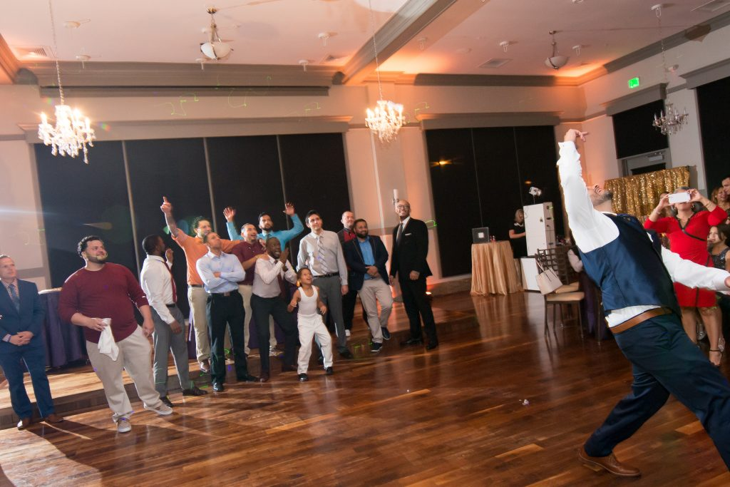 Groom tossing garter | Classic Purple & White Wedding Photography Noah's Event Venue Orlando Florida Anna Christine Events Wedding Planner Jessica Leigh